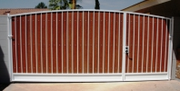 simple arched RV gate with redwood composite slats and white paint