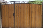 a decorative arched driveway gate with medium stained clear ceda