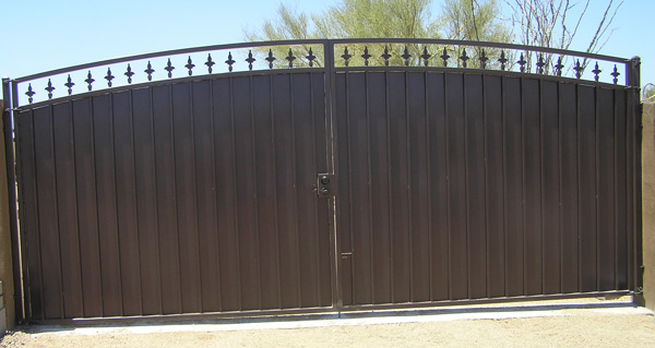 arched decorative gate with steel plate and fleur de lis spears